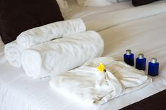 Rolled towels and bathrobe on bed royalty free stock photo