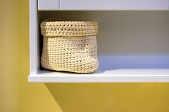 Rolled towels with wicker basket on shelf of rack background royalty free stock photos