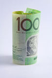 Rolled up Australian 100 dollar note. On white background Stock Photos