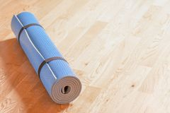 Rolled up blue yoga mat on the floor stock photo
