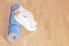 Rolled up blue yoga mat with white sneakers on the floor royalty free stock image