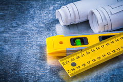 Rolled up blueprints ruler and construction level Stock Photography