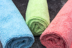 Rolled Up Cleaning Cloths. An image of three coloured Cleaning Cloths rolled up on a black surface Stock Photo