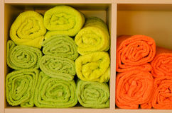 Rolled-up colorful towels in a shelf Stock Photos