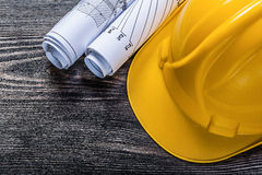 Rolled up construction plans hard hat on wooden board maintenanc Stock Photography