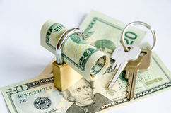 Rolled up dollar bill in padlock on bank notes and keys Stock Photography