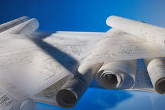Rolled-up drawings. Many different rolled-up engineering drawings on desk with blue background Stock Photo