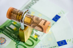 Rolled up euros in padlock on bank notes Royalty Free Stock Photo