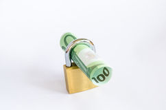 Rolled up euros in padlock Stock Photography