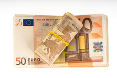 Rolled up euros with rubber on the fifty euro banknotes pile. Money bunch stack Stock Image
