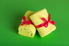Rolled up green beach towel. On green background Stock Image