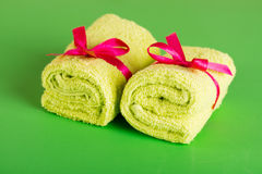 Rolled up green beach towel. On green background Stock Photos