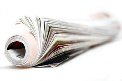 Rolled up magazine. On white Stock Images