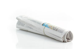 Rolled up newspaper 2. Rolled up newspaper with rubberband on white reflecting background Royalty Free Stock Photography
