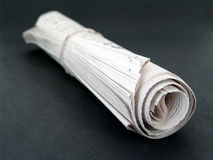 Rolled up newspaper Stock Image