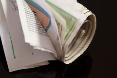 Rolled up newspaper on black Stock Images