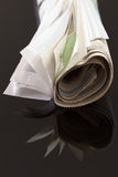 Rolled up newspaper on black 2 Royalty Free Stock Photography