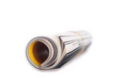 Rolled up newspaper on white stock photography