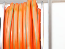 Rolled up of orange plastic hose Stock Photography
