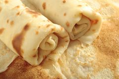 Rolled-up pancakes. Close up view on two freshly prepared rolled up pancakes arranged on single flat pancake Royalty Free Stock Photography