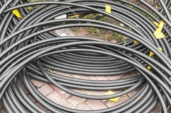 Rolled up PVC cables lying on brick floor stock image
