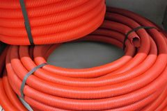 Rolled-up red supply hose. Rolled-up supply hose , strapped and stacked Royalty Free Stock Photos