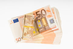 Rolled up with rubber on the fifty euro banknotes pile. Money bunch stack Royalty Free Stock Image