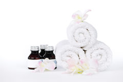 Rolled up spa towels. White rolled up spa towels and body care products with orchid flowers Stock Photography