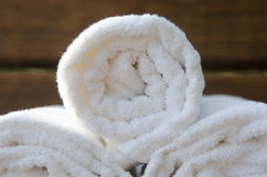 Rolled up Towel. A close up of three rolled towels on a wooden spa bench royalty free stock photo