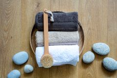 Rolled up towels and body dry brush for male exfoliation. Shower, Turkish bath or ayruvedic massage over zen pebbles and design wooden background, above view Stock Photos