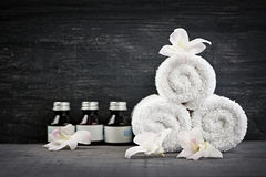 Rolled up towels and products at spa Stock Photography