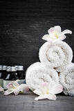 Rolled up towels and products at spa Stock Photo
