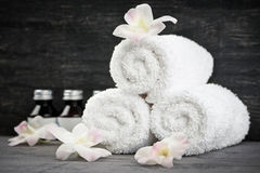 Rolled up towels at spa. White rolled up towels with body care products at spa royalty free stock photos