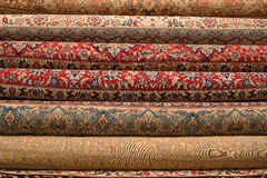 Rolled-up turkish or persian carpets. In a variety of colors in a carpet store Stock Photo