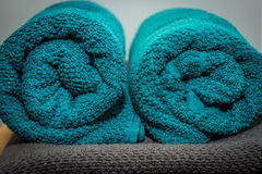 Rolled up turquoise towels located on a gray towel.  royalty free stock photography