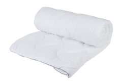 Rolled white blanket isolated. Rolled white blanket on white isolated background Royalty Free Stock Photos