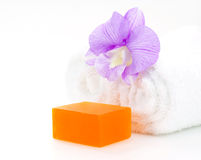 Rolled white towel, soap and orchid Royalty Free Stock Photos