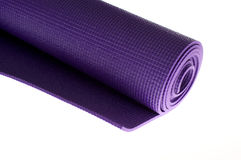 Rolled yoga mat on white. A rolled up yoga or pilates exercise mat isolated on white Royalty Free Stock Photography