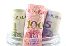 Rolled yuan in glass jar royalty free stock image
