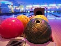Rollen gesprengt Innenraum des Bowlingbahnwegs mit Bällen bringt Maschinennahaufnahme, selektiven Fokus auf blauem Ball zurück lizenzfreies stockfoto