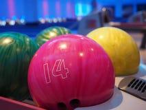 Rollen gesprengt Innenraum des Bowlingbahnwegs mit Bällen bringt Maschinennahaufnahme, selektiven Fokus auf blauem Ball zurück lizenzfreie stockfotos