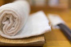 Rollen herauf weißes Tuch für die Hand, die auf der Bambusplatte im japanischen Restaurant abwischt Stockfoto