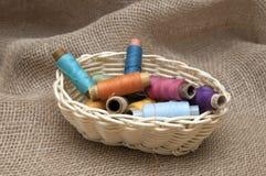Rollen met kleurrijke draden in een rieten mand Stock Afbeeldingen