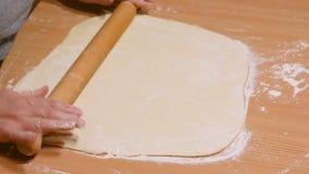Rollen Sie den Teig mit Nudelholz auf Holztisch stock video