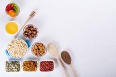 Rollen Sie mit Bestandteilen für das Kochen des selbst gemachten Granolas auf weißem Hintergrund Gesundes snak Stockbilder