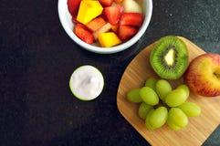 Rollen Sie mit Obstsalat und etwas Jogurt auf einem Granit Countertop, der von direkt oben gesehen wird Stockbilder
