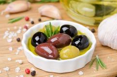 Rollen Sie mit verschiedenen Oliven im Olivenöl und in den Gewürzen auf Holz Lizenzfreie Stockfotografie
