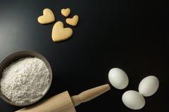 Rollen Sie mit Weizenmehl, -Nudelholz und -eiern Stockfoto