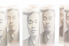 Rollen Sie oben von Geld-Yen Banknote On Vintage Wooden-Hintergrund Stockbild