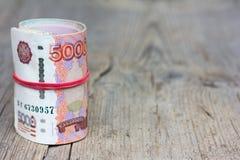 Rollen Sie russische Banknoten auf altem grauem hölzernem Brett mit Sprüngen Stockbilder